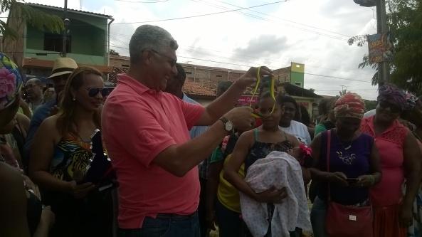 O prefeito Zé Martins entrega a faixa de Prefeito Bebê Quilombola para Alice Sofia Rodrigues (Ariquipá)